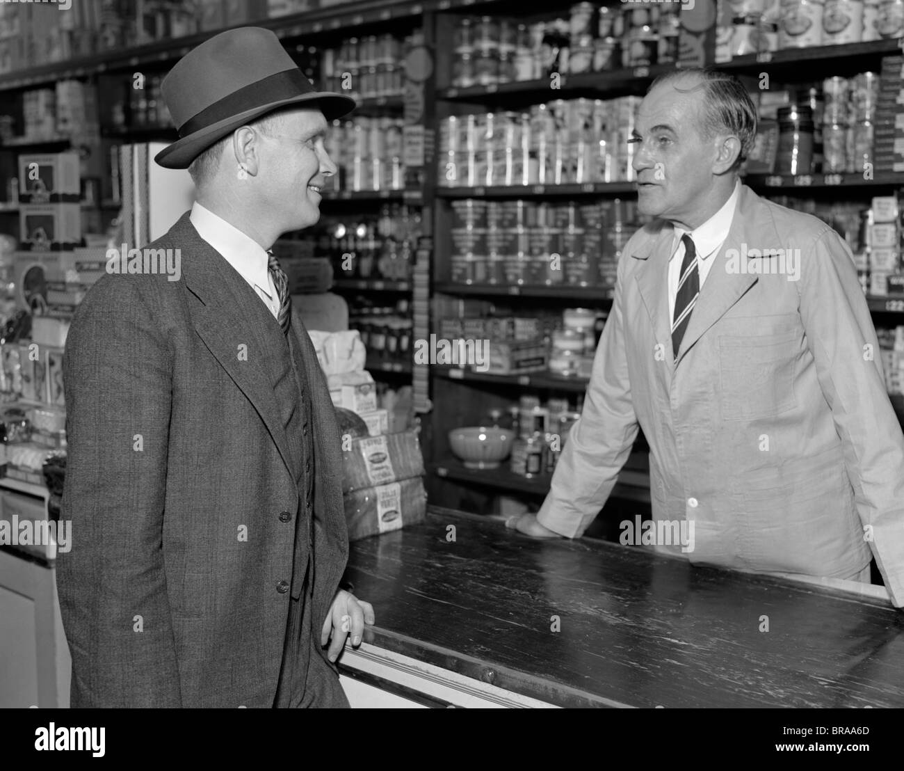 1930s TWO MEN CLERK AND CUSTOMER TALKING OVER COUNTER IN RETAIL GENERAL STORE - Stock Image