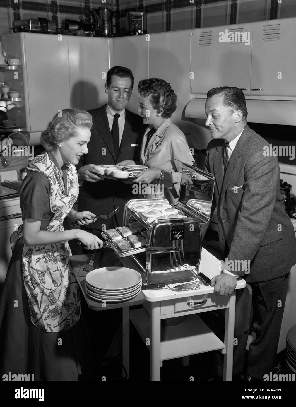 1950s 2 COUPLES IN KITCHEN WOMAN COOKING HAM & EGGS IN CHROME BROILER - Stock Image