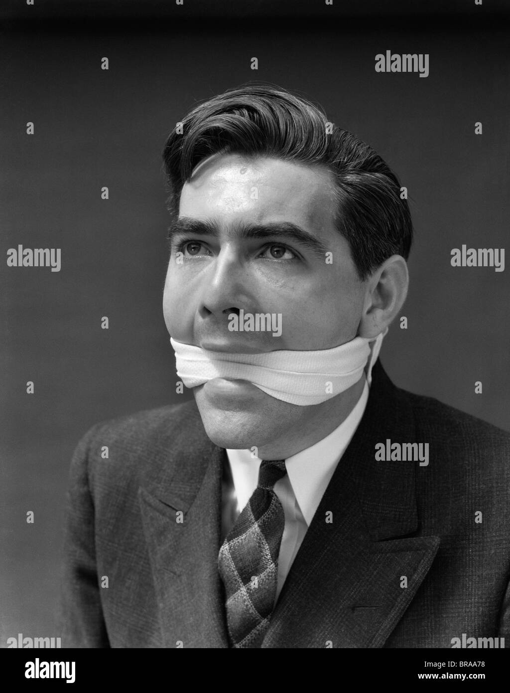 1930s PORTRAIT OF MAN WITH GAG IN MOUTH - Stock Image