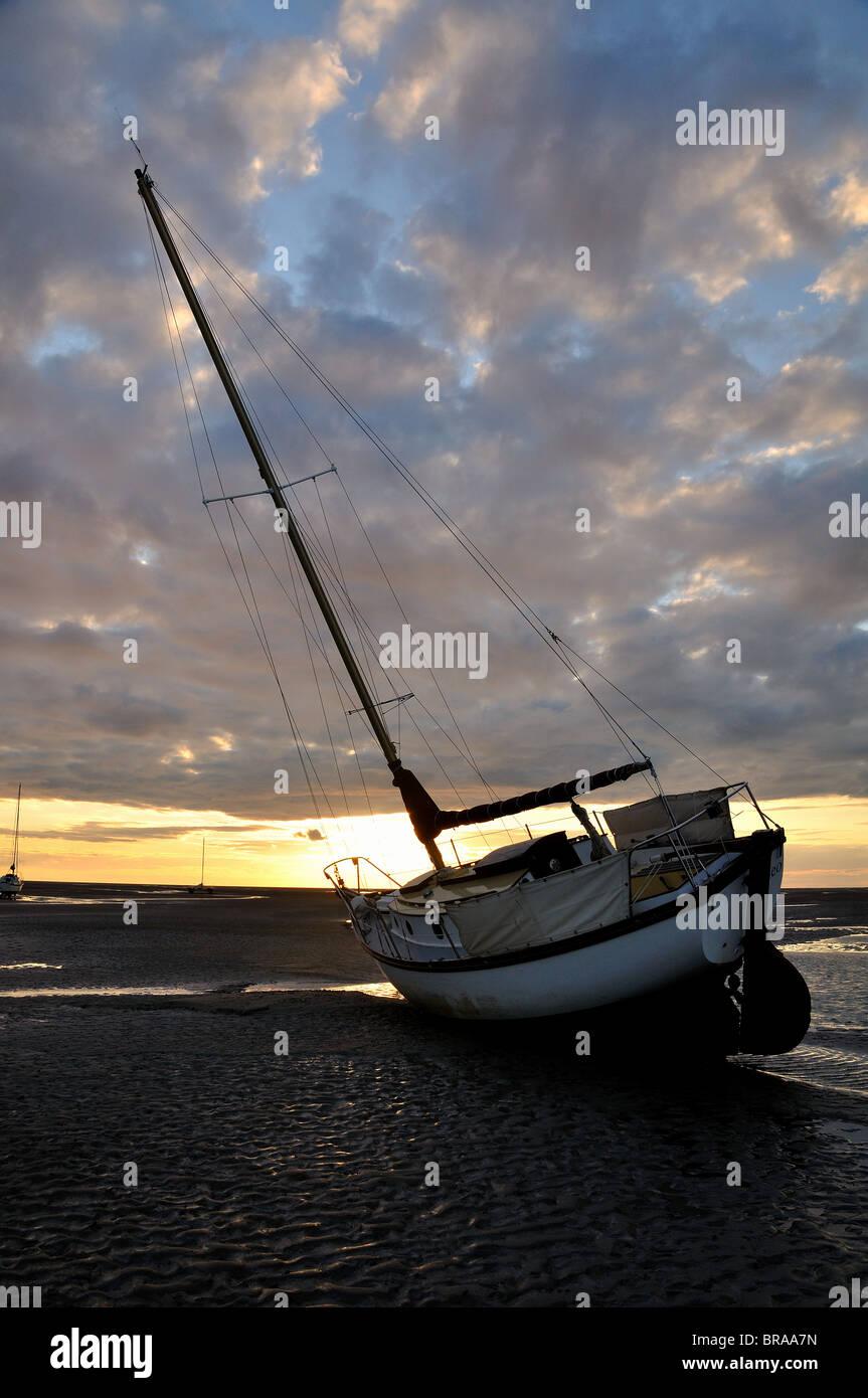 Boat at Meols Beach at sunset at low tide - Stock Image