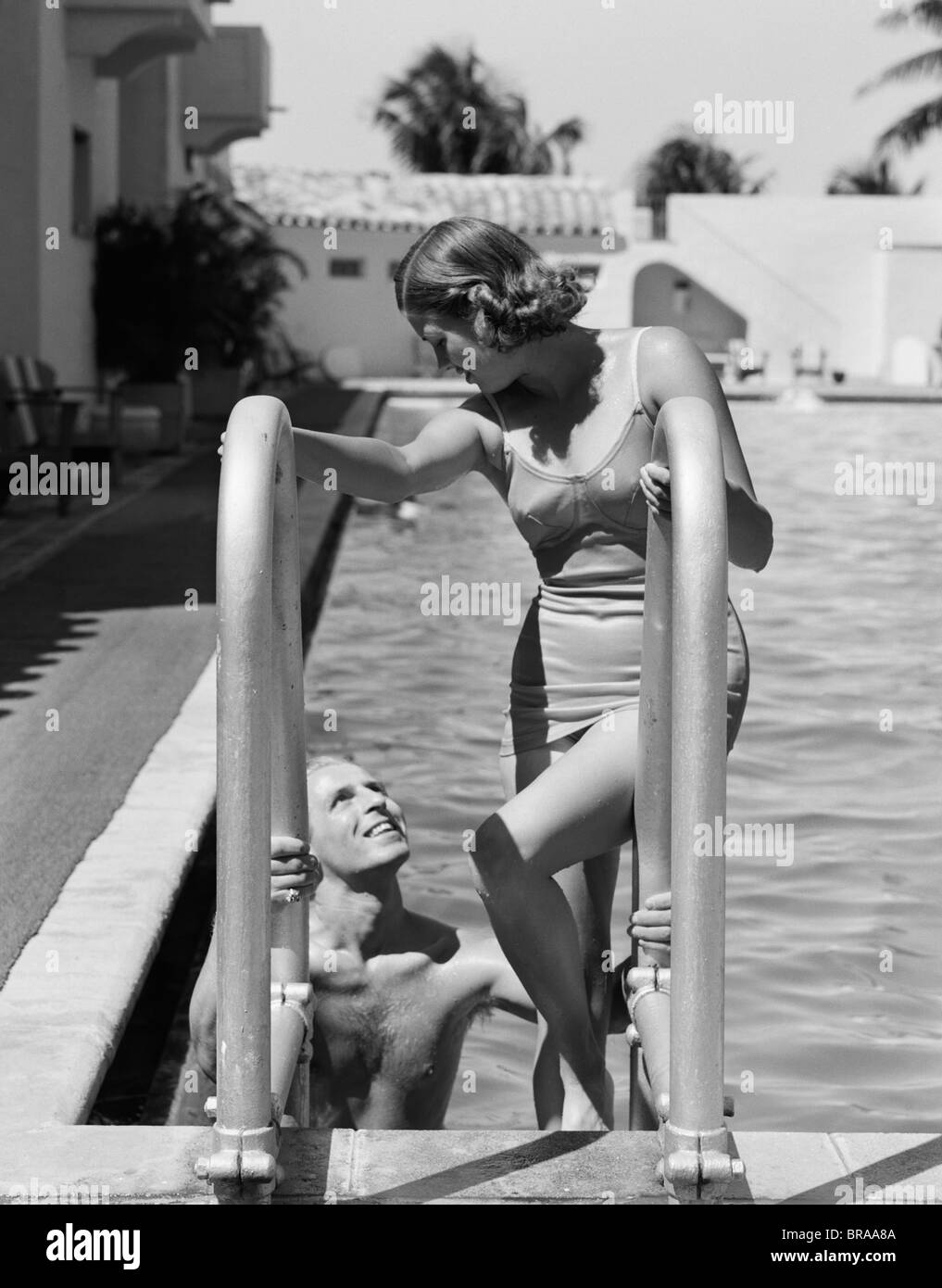 1930s WOMAN WEARING ONE PIECE BATHING SUIT CLIMBING OUT OF SWIMMING POOL LOOKING DOWN AT MAN SMILING - Stock Image