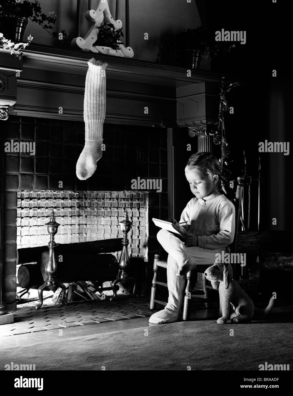 1940s LITTLE GIRL SITTING BESIDE FIREPLACE WITH ONE CHRISTMAS STOCKING WRITING A LETTER Stock Photo
