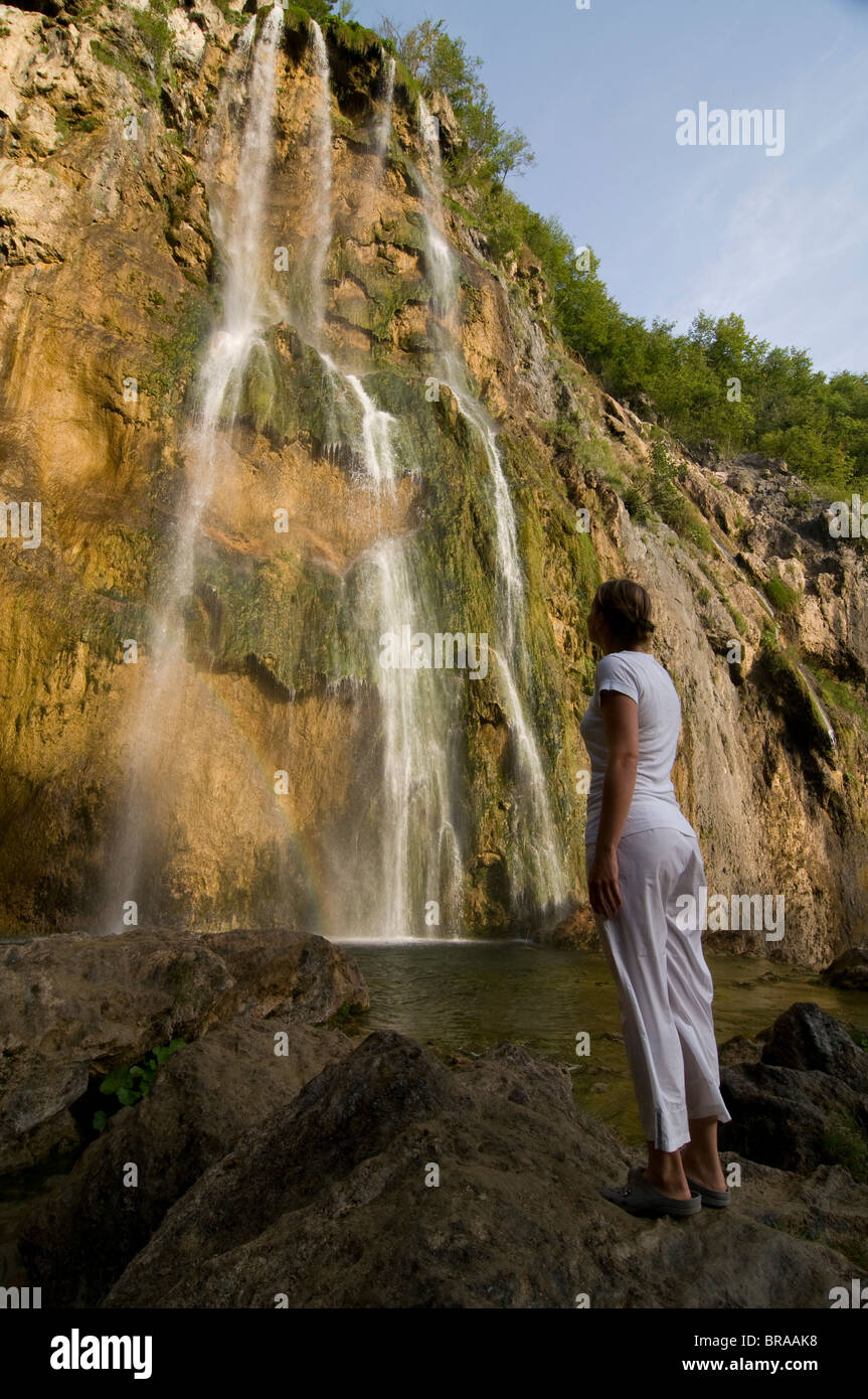 Woman looking at a giant waterfall, Plitvice Lakes National Park, UNESCO World Heritage Site, Croatia, Europe - Stock Image