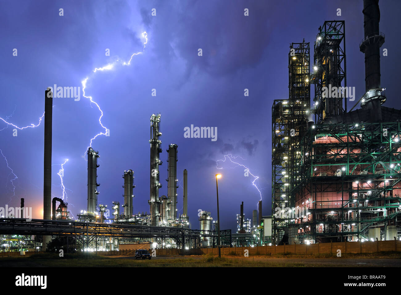 Lightning during thunderstorm above petrochemical industry in the Antwerp harbour, Belgium - Stock Image