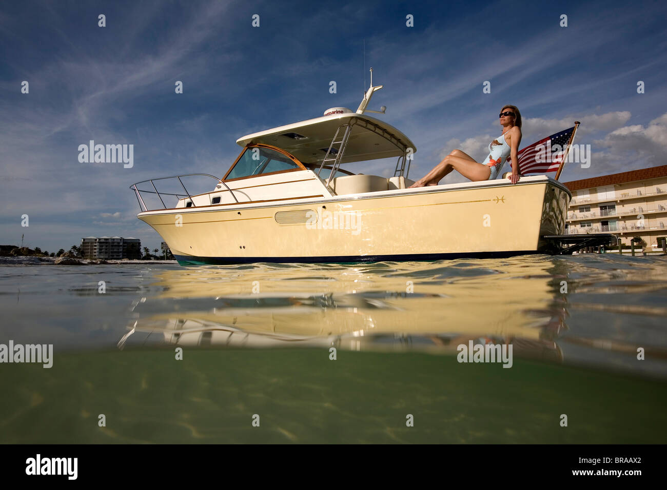 Woman relaxing on the stern of a Surf Hunter 29 Inboard off Marco Island, Florida, USA. Model and property released - Stock Image