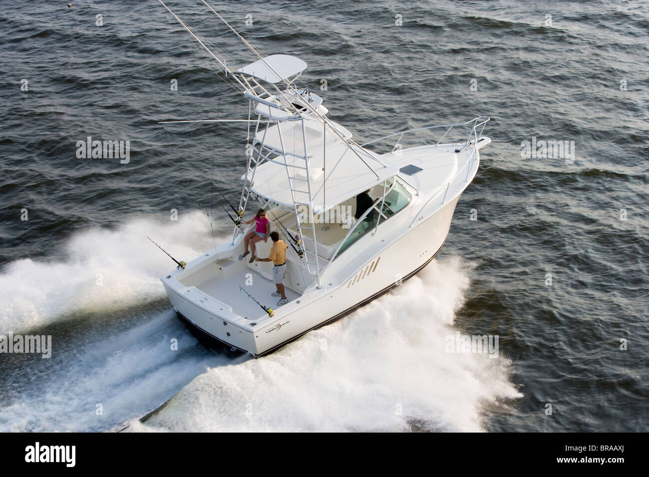 Couple on the aftdeck of a sportsfisher.  Model and property released. - Stock Image