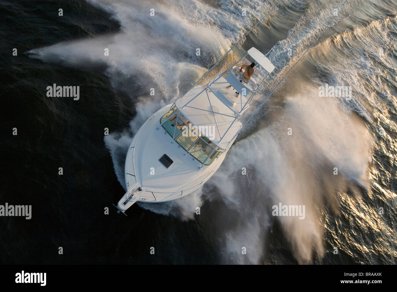 Man steering a sportfisher boat from the tuna tower.  Model and property released. - Stock Image