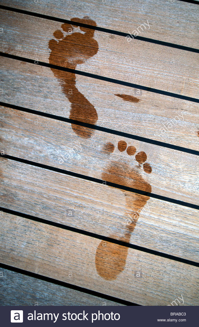Wet footprints on a yacht's teak deck. - Stock Image
