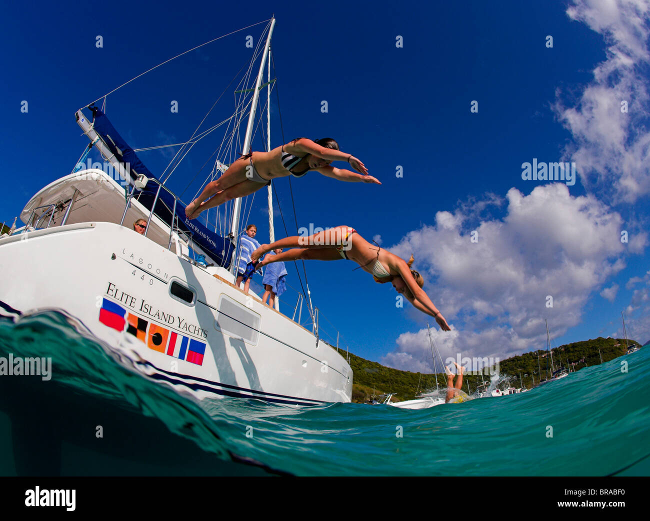 Two girls diving from a catamaran into the sea, British Virgin Islands, Caribbean, December, 2006 - Stock Image