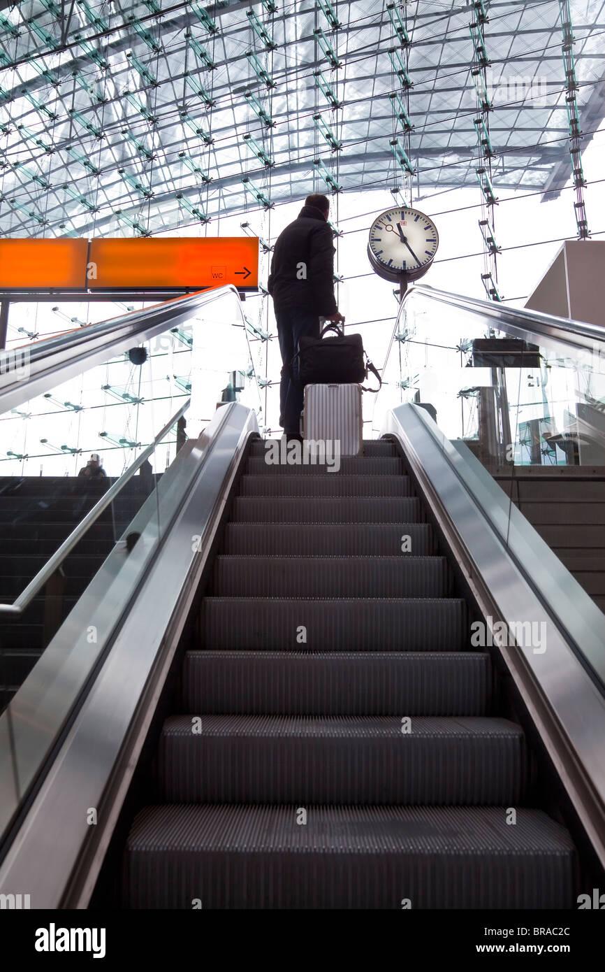 Escalator and platform clock at modern train station, Berlin, Germany, Europe - Stock Image