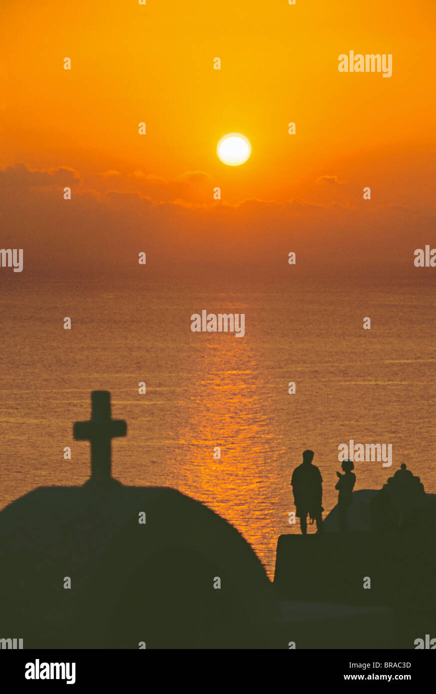 Church and couple silhouetted at sunset, Santorini, Cyclades, Greek Islands, Greece, Europe - Stock Image
