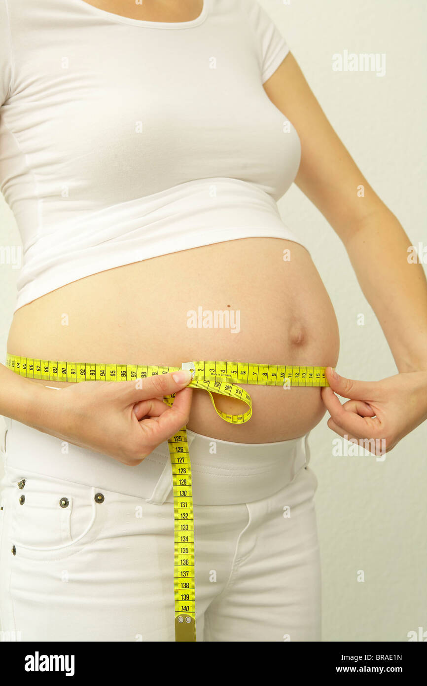 Pregnant woman measuring abdominal girth - Stock Image