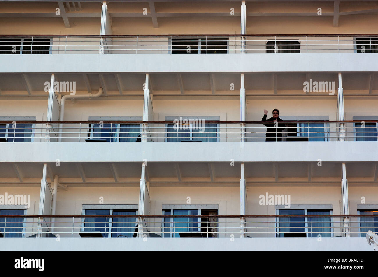 The cabins of a cruise ship with a woman waving - Stock Image