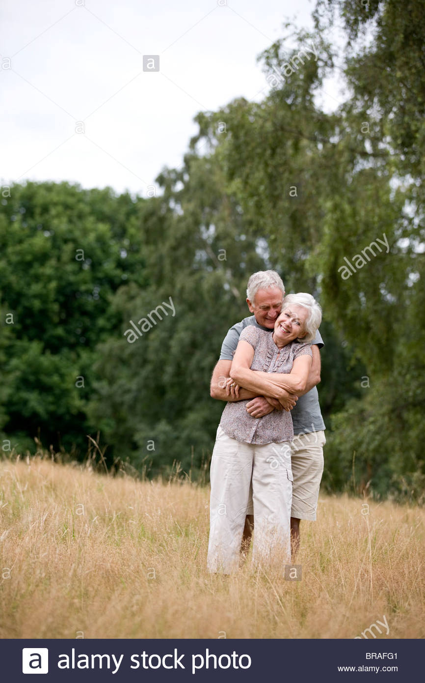 A senior couple standing in a field, embracing - Stock Image