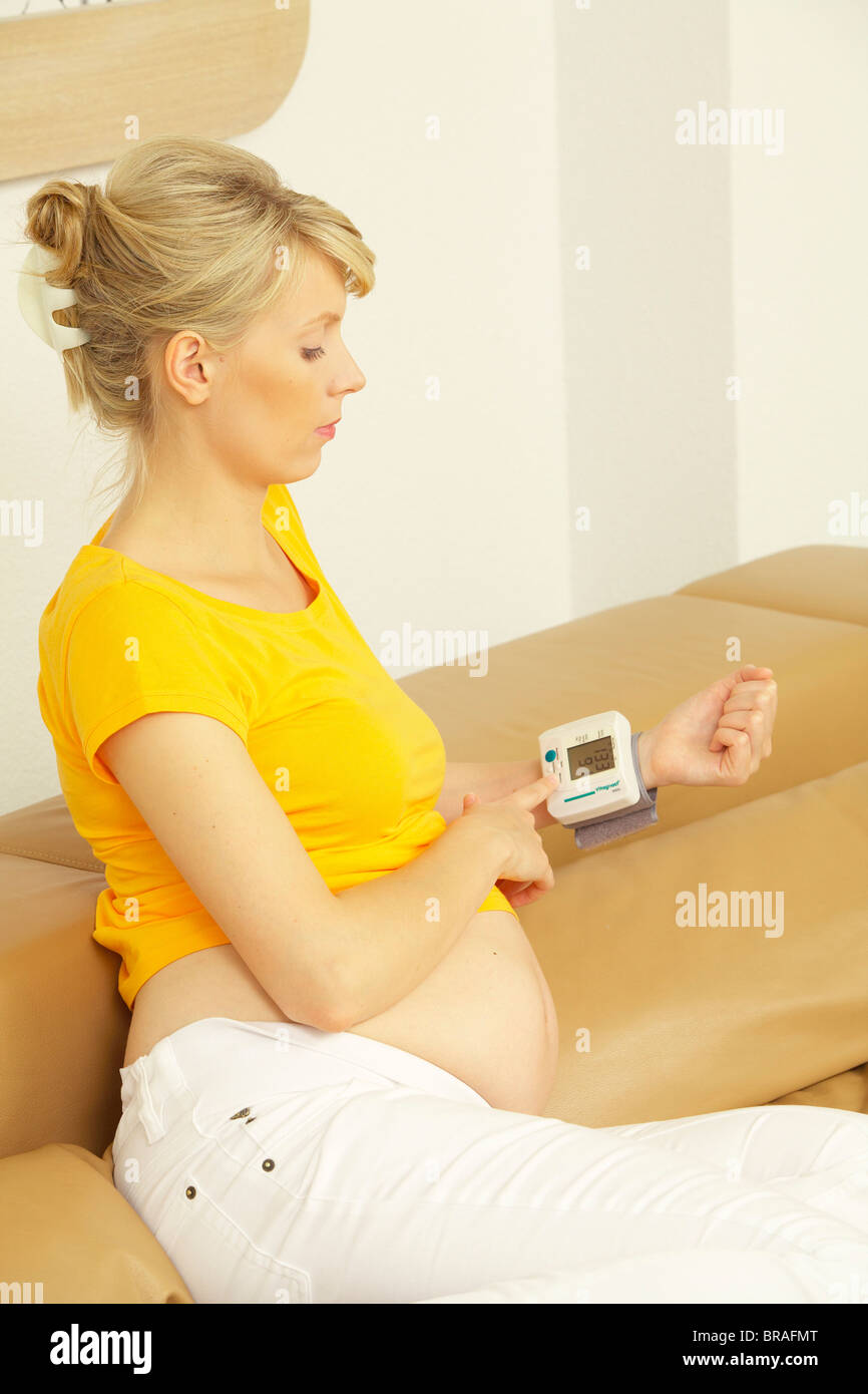 Pregnant woman checking blood pressure - Stock Image