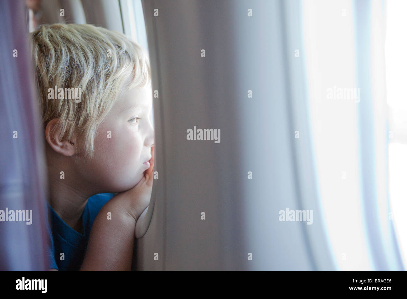 Young boy staring out plane window Stock Photo