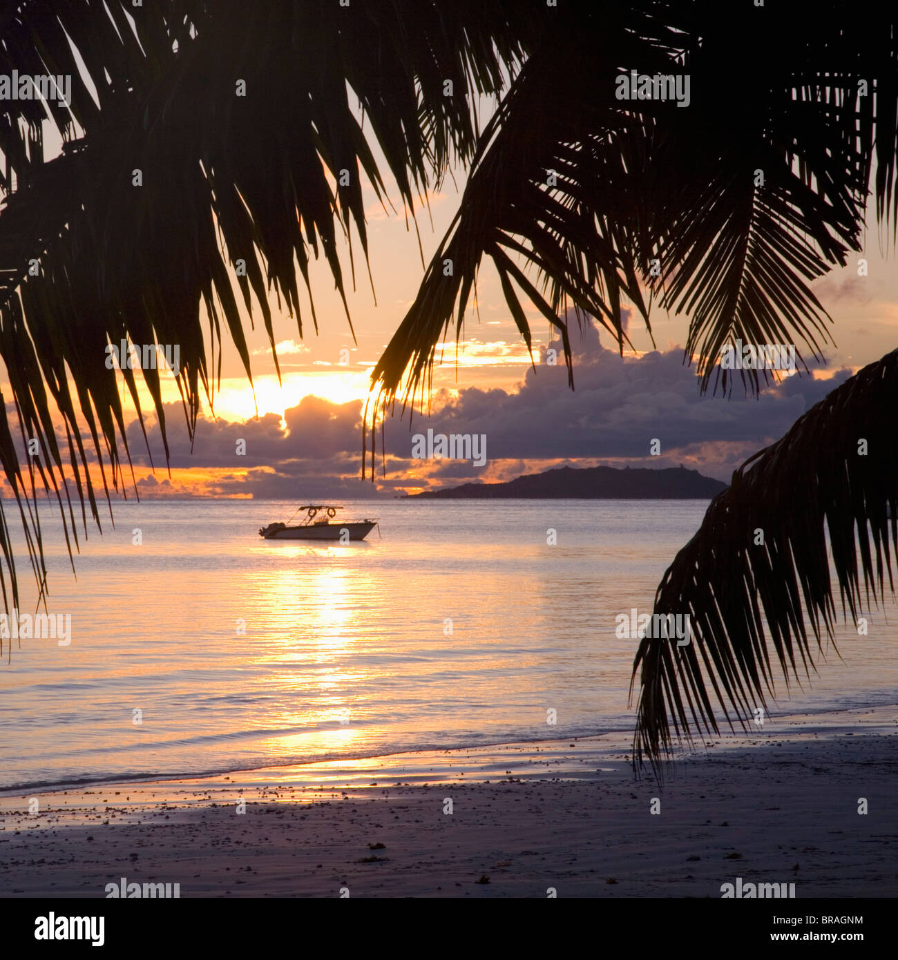 Small boat moored off the beach at Anse Volbert at sunrise, Baie Sainte Anne district, Island of Praslin, Seychelles Stock Photo