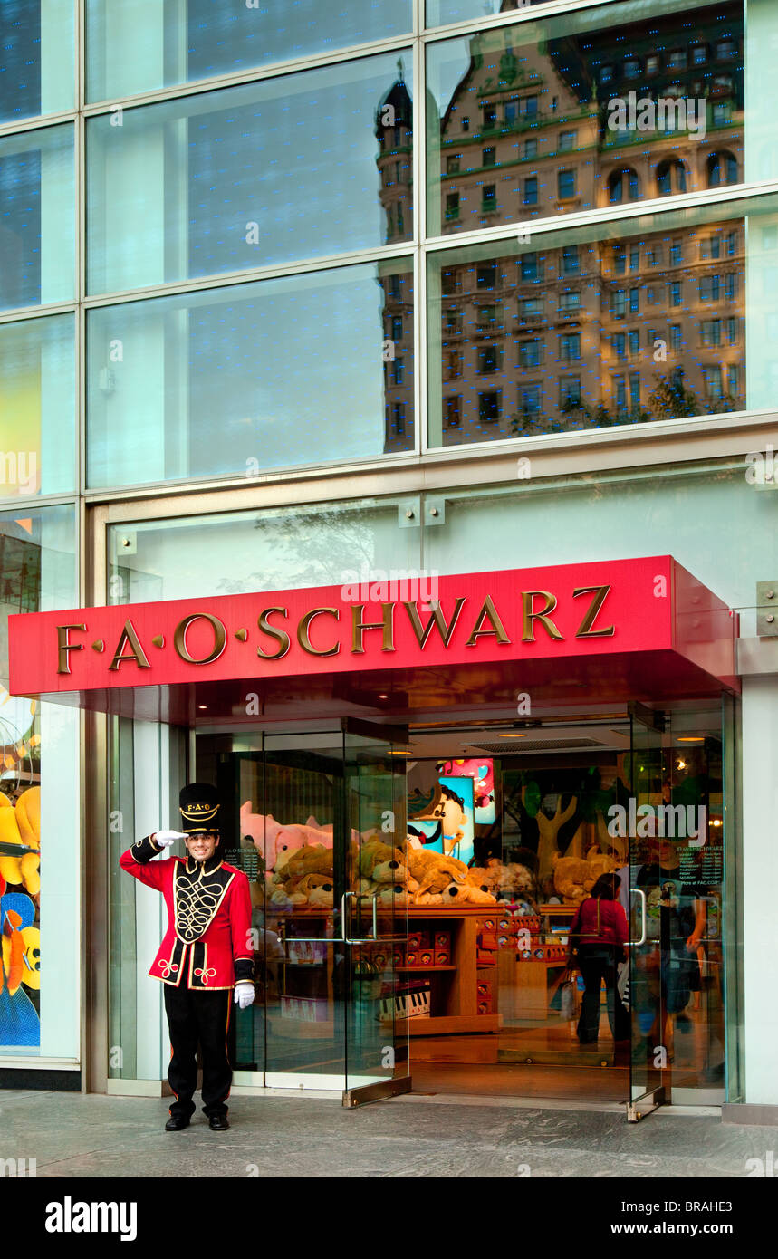 Royal salute from the doorman at FAO Schwarz toy store with reflection of the Plaza Hotel in Manhattan, New York - Stock Image