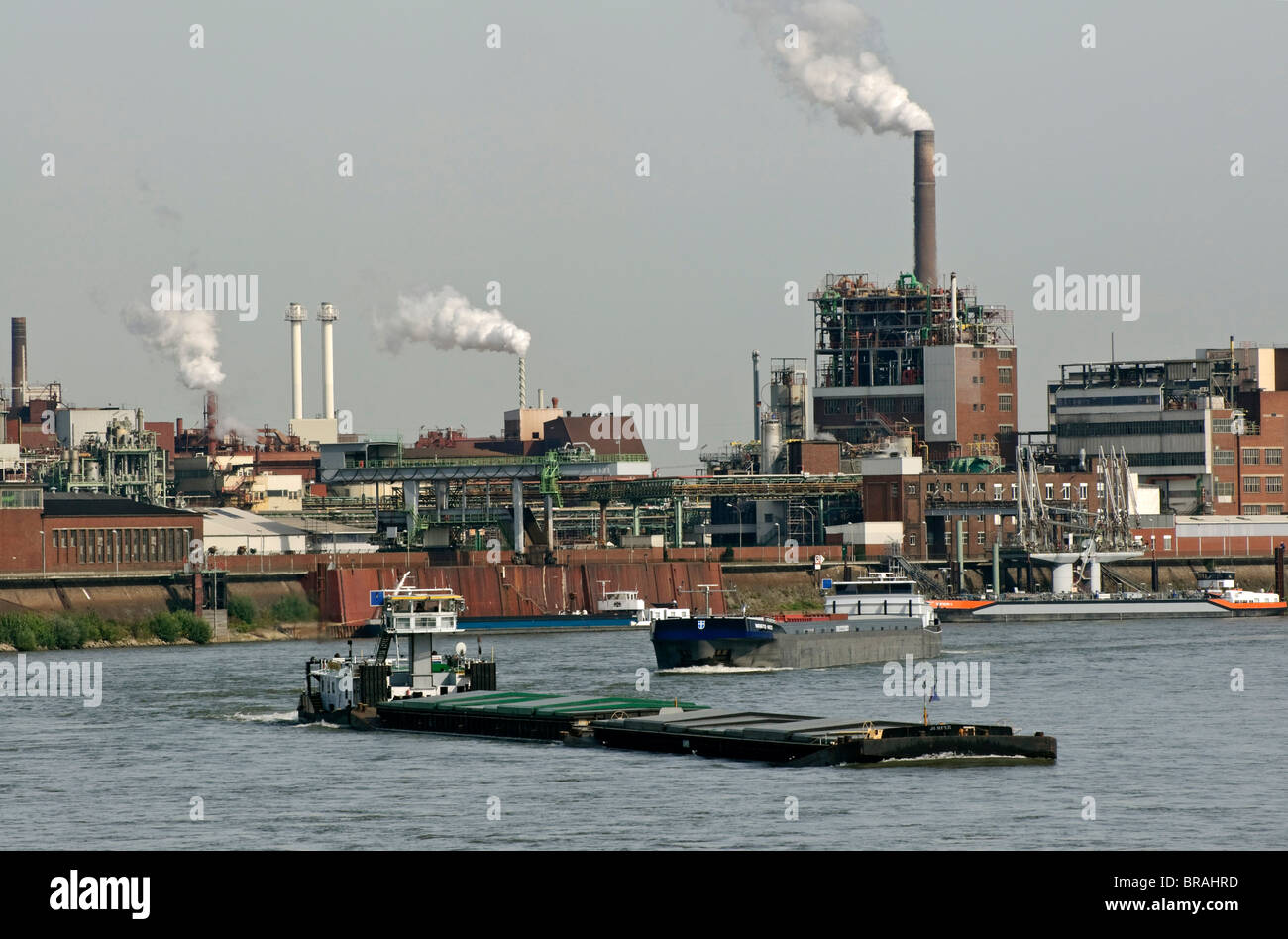 Boat traffic on the Rhine with Chempark Krefeld in background, NRW, Germany. - Stock Image