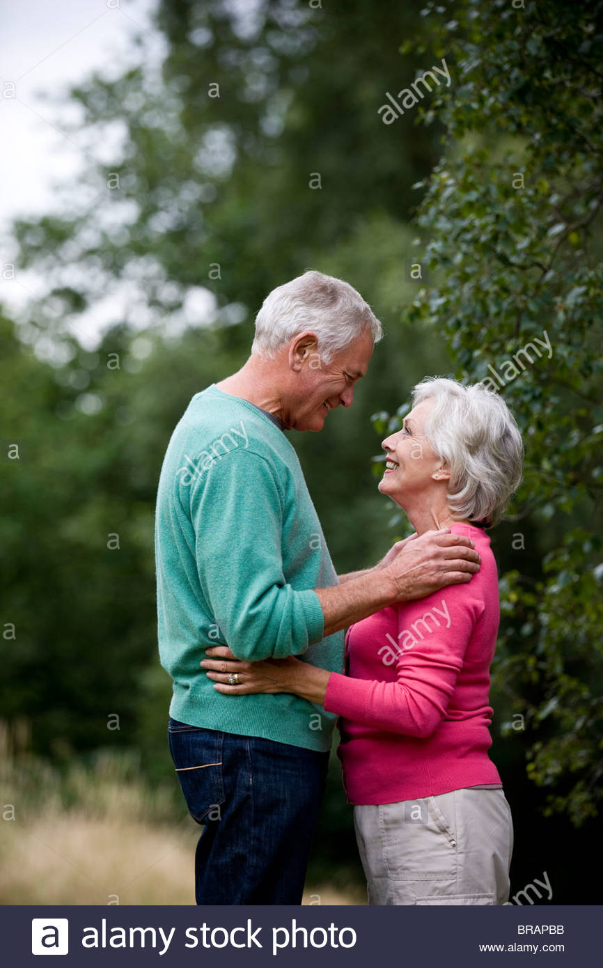 A senior couple looking into each other's eyes, outdoors - Stock Image