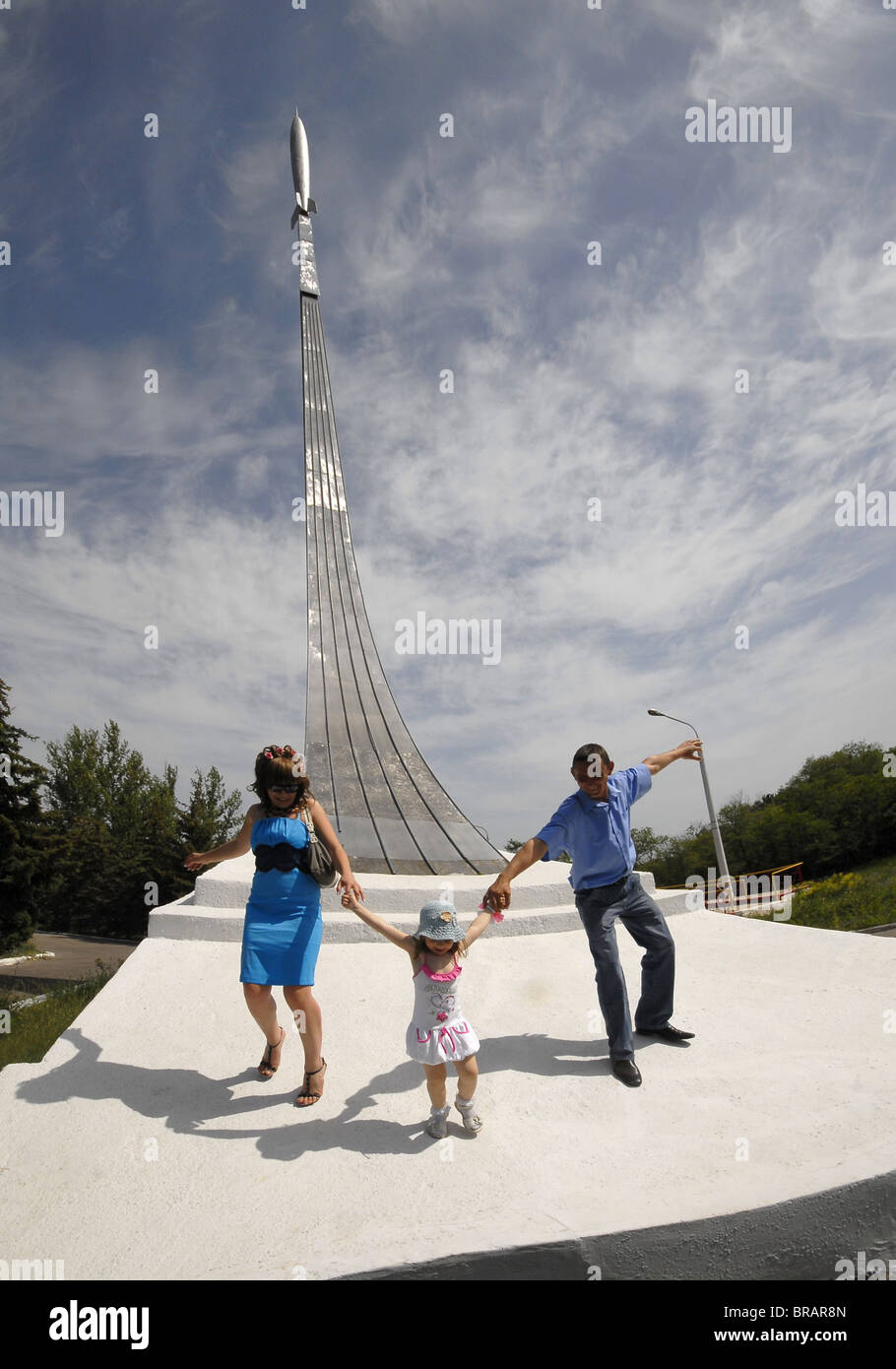 The family plays at a monument a place of a landing of the first cosmonaut in Jury Gagarin's world. - Stock Image