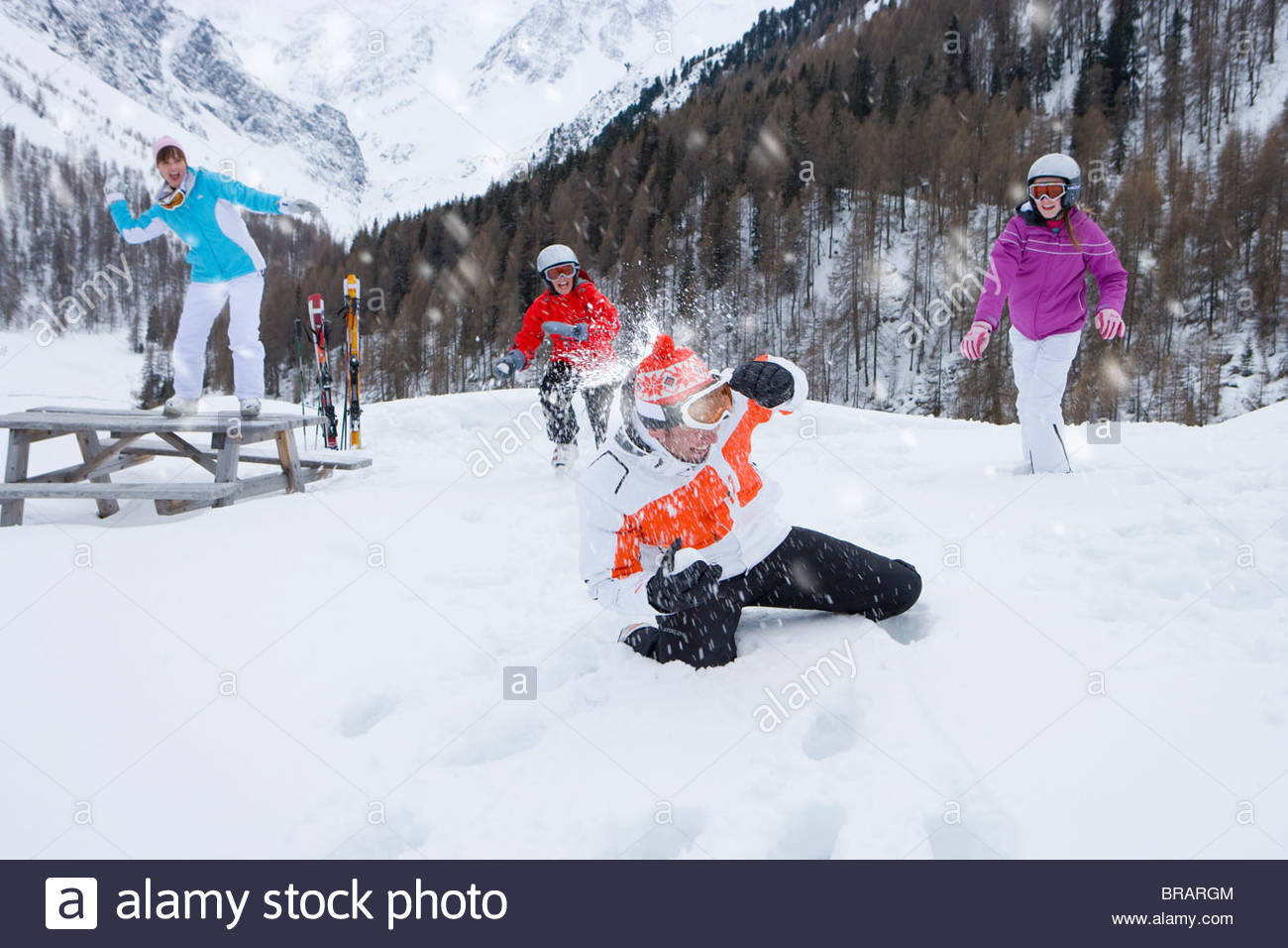 Family having snowball fight in valley - Stock Image