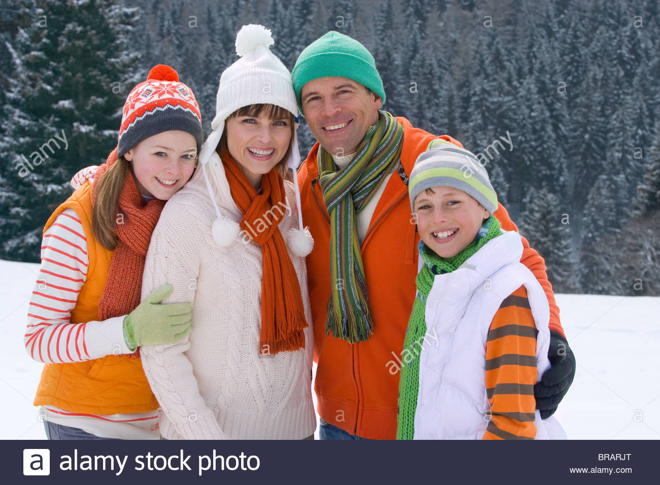 Family in caps and scarves standing together in snow - Stock Image
