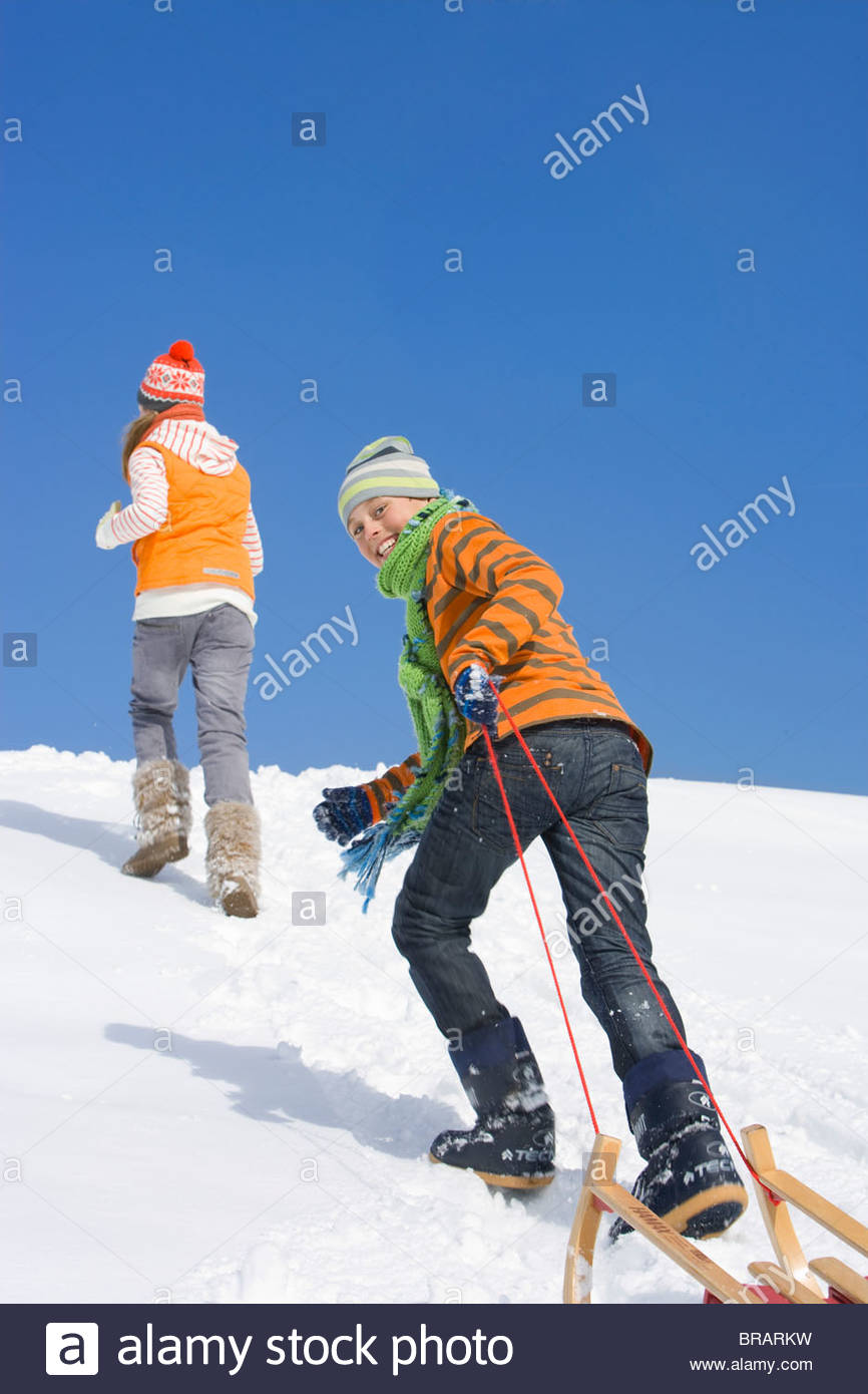 Brother and sister pulling sled up hill on ski slope - Stock Image