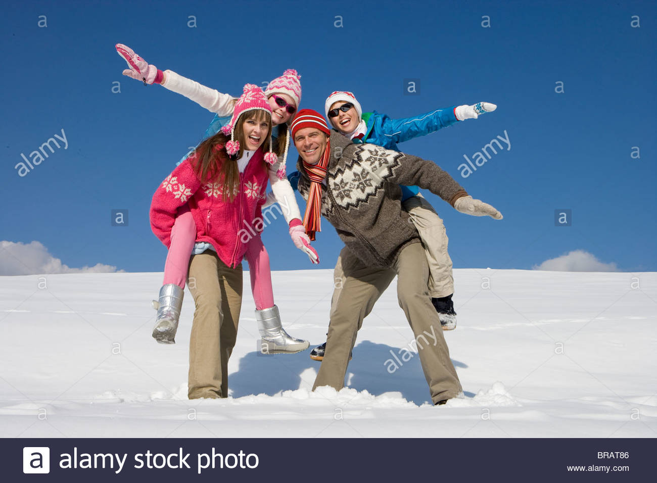 Parents giving children piggyback ride while standing in snow - Stock Image
