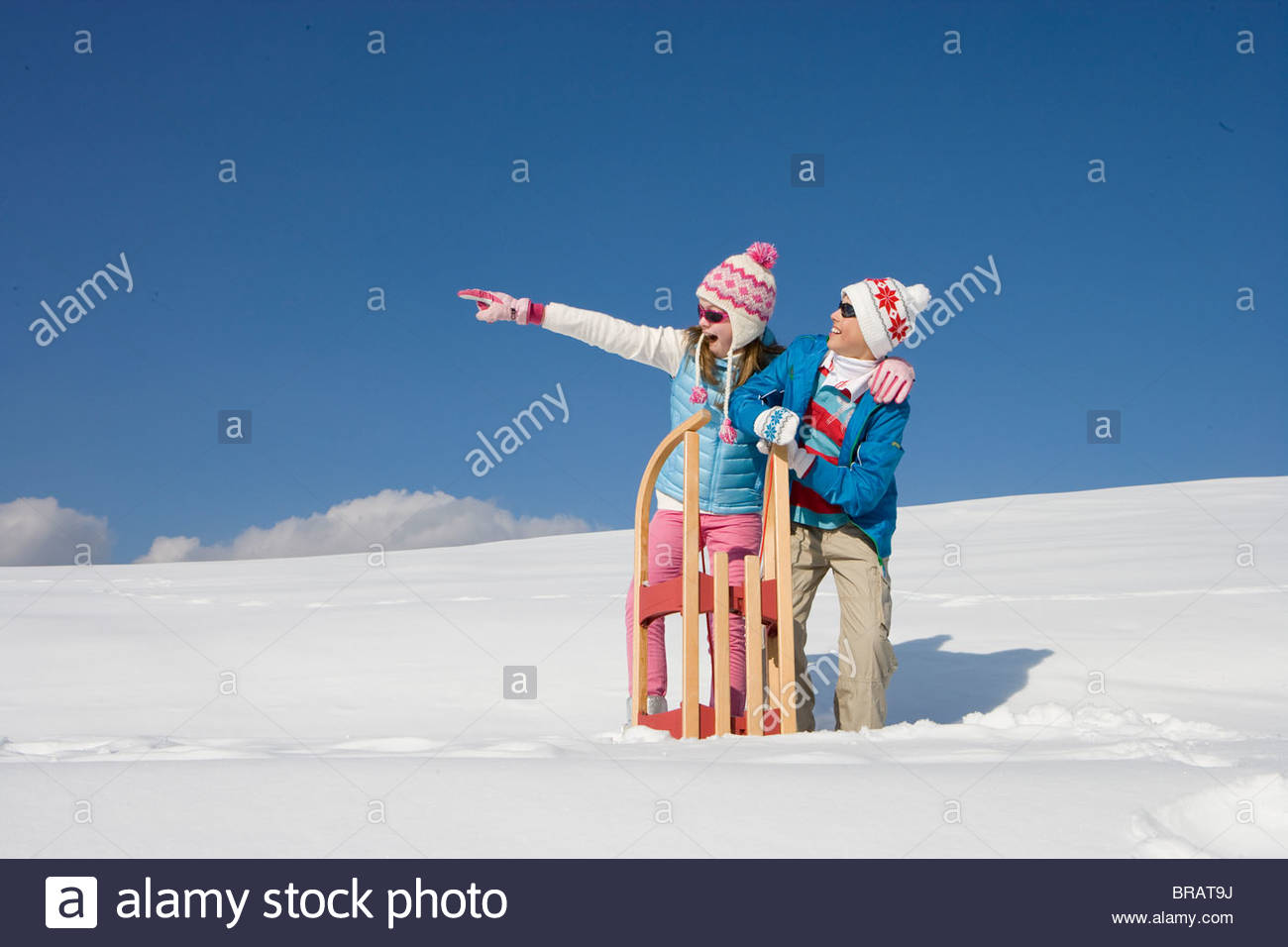 Girl pointing something out for brother while standing in snow with sled - Stock Image