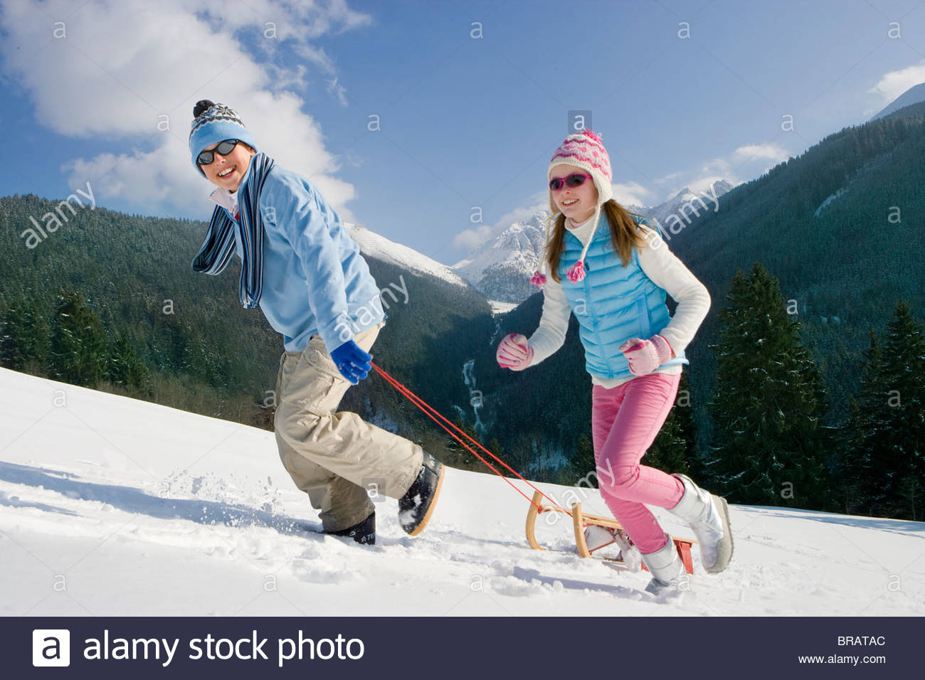 Brother and sister pulling sled uphill - Stock Image