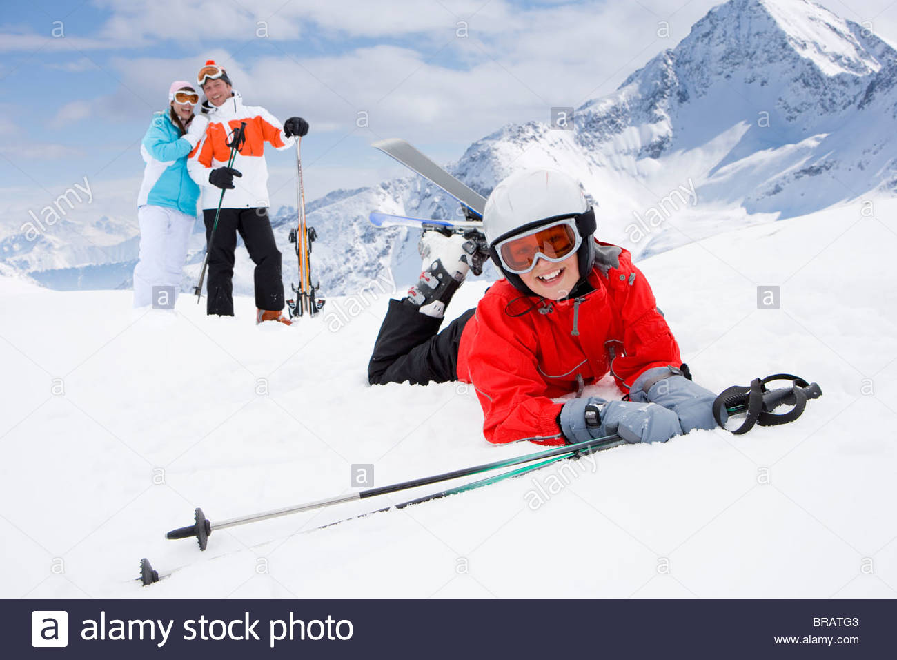 Boy on skis falling in snow while parents watch - Stock Image