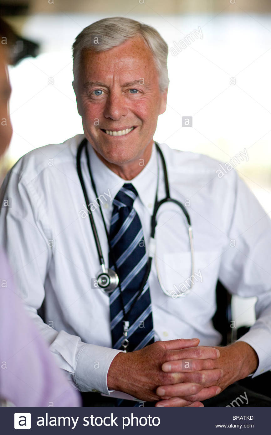 Smiling doctor with stethoscope with hands clasped - Stock Image