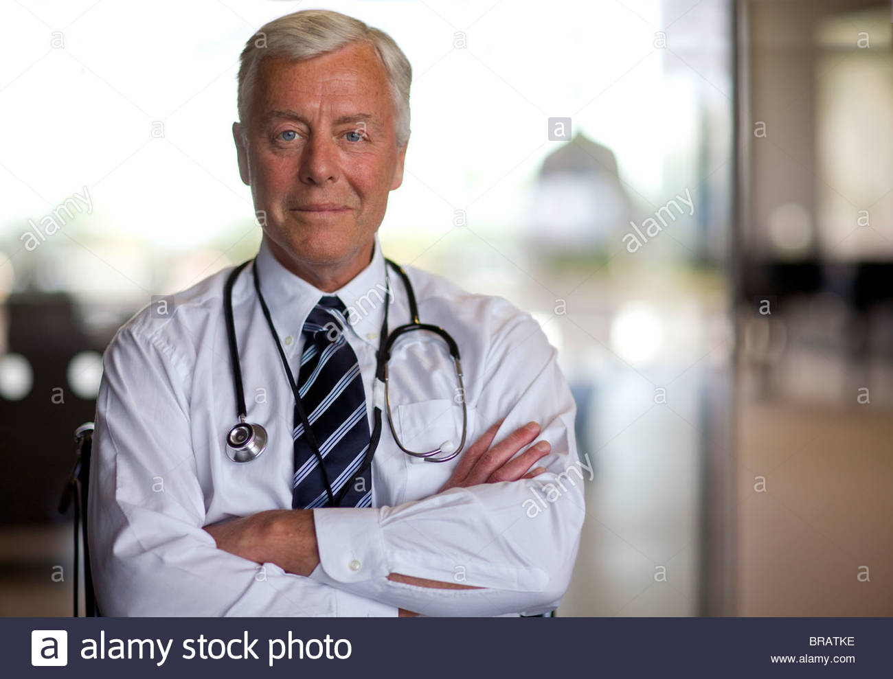 Serious doctor with stethoscope and arms crossed - Stock Image