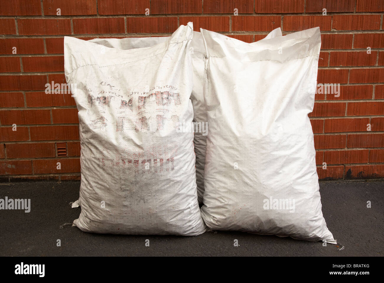bags of coal in plastic 25kg bags delivered leaning against a red brick house wall in the uk - Stock Image