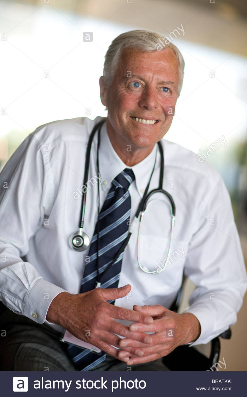 Smiling doctor with stethoscope and hands clasped - Stock Image