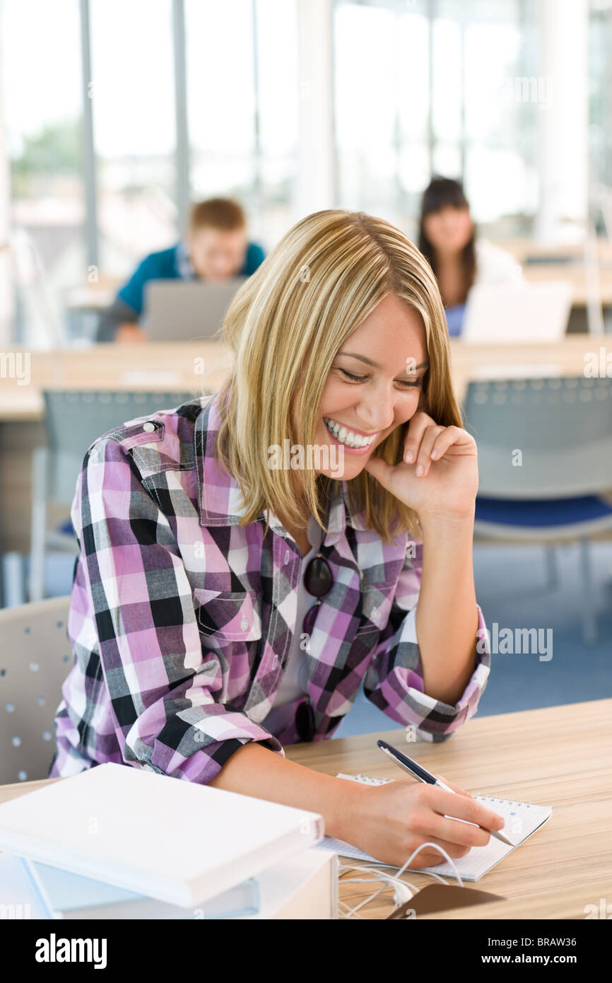 Happy smiling student study in classroom at university, schoolmates in background - Stock Image