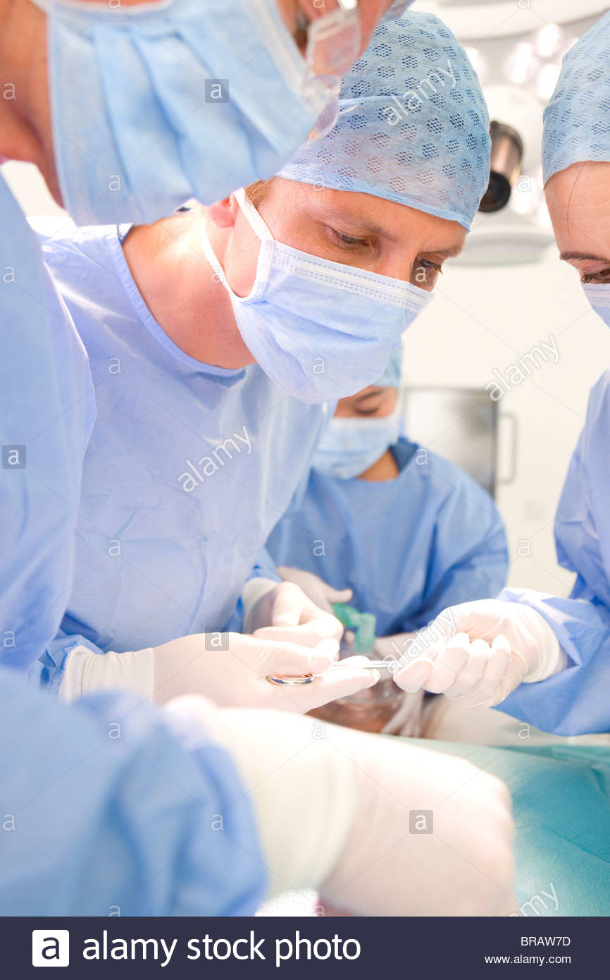 Surgeons performing operation in hospital operating room - Stock Image