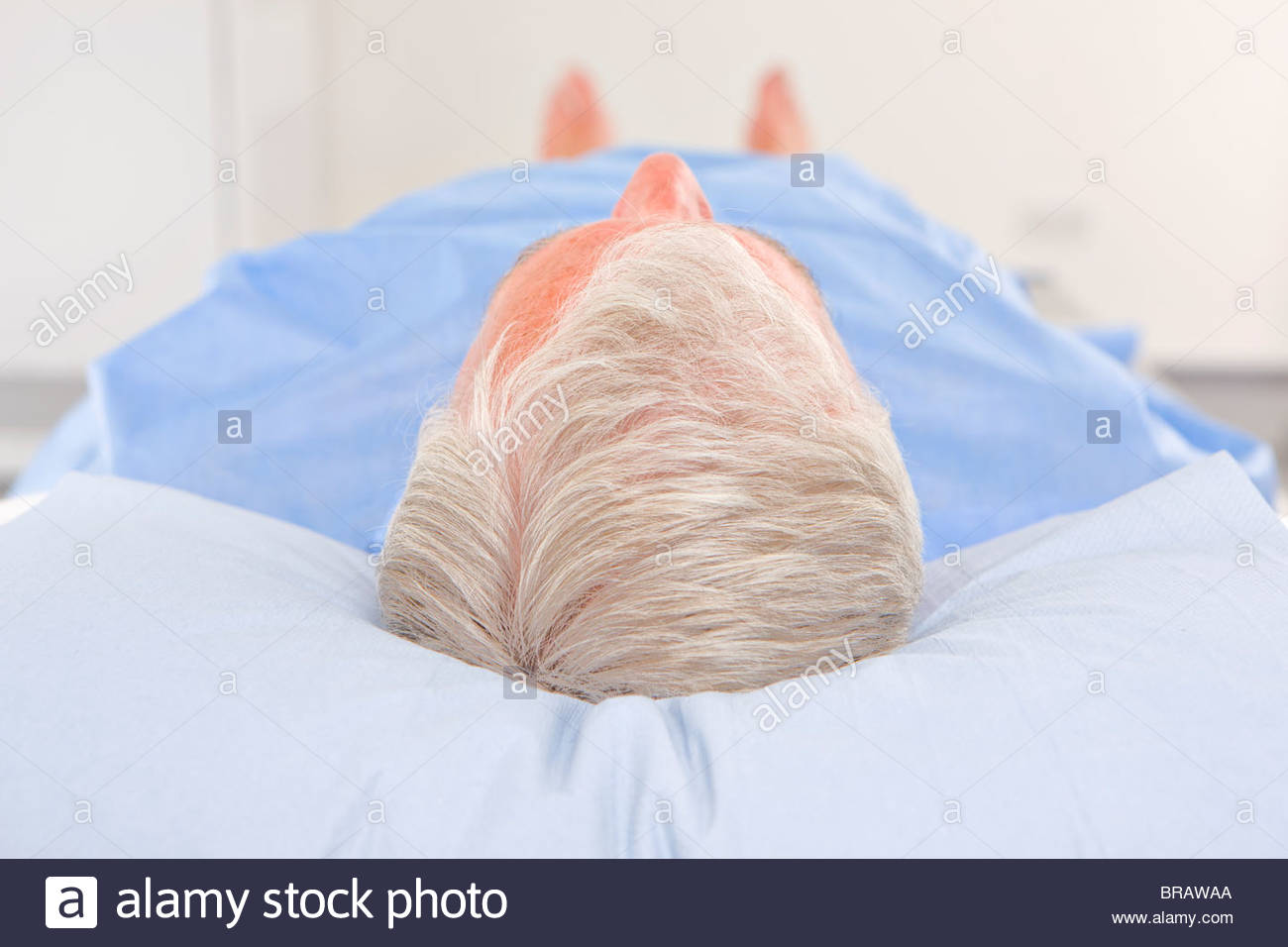 Patient laying on examination table in hospital - Stock Image