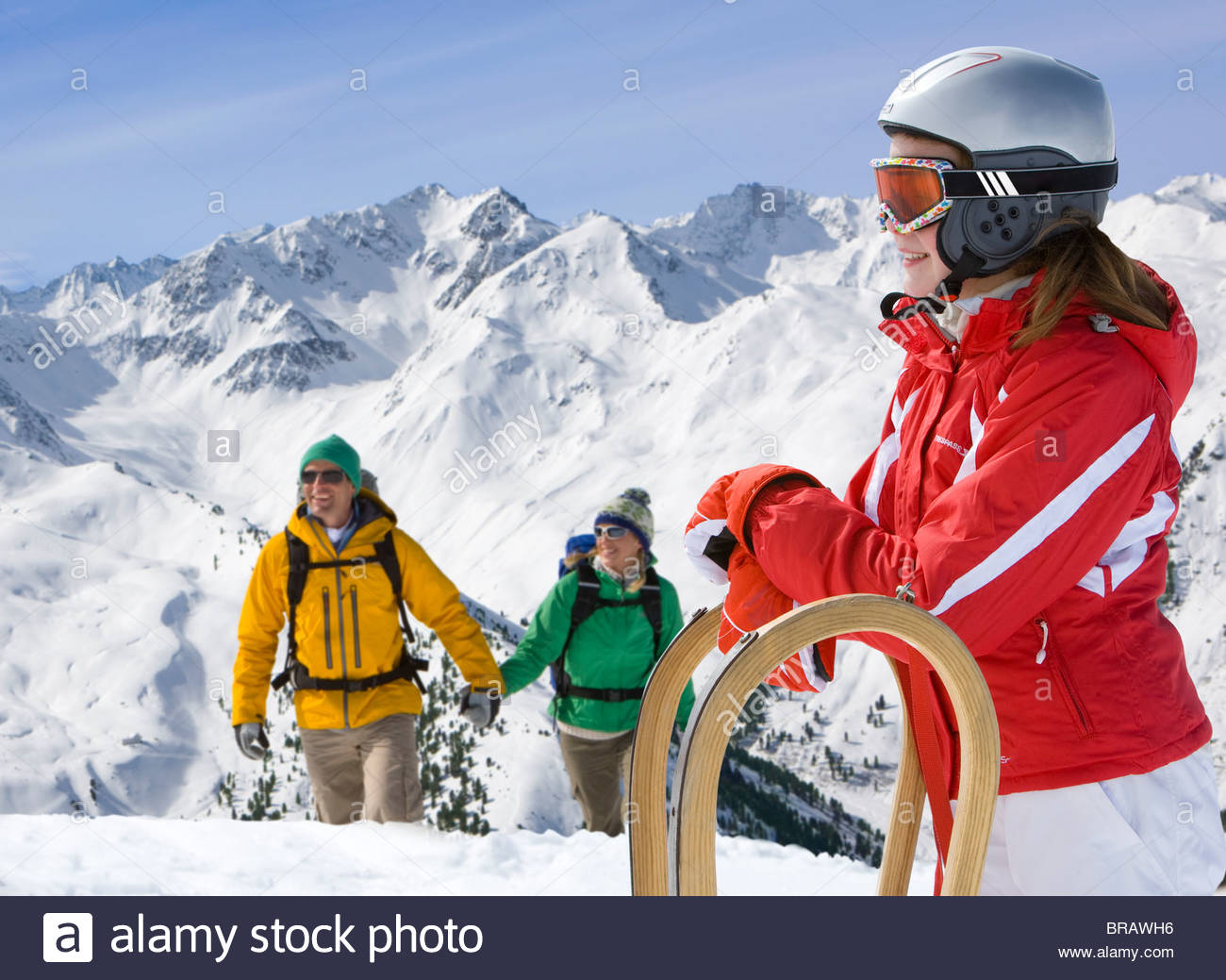 Girl standing in snow with sled, hikers nearby - Stock Image