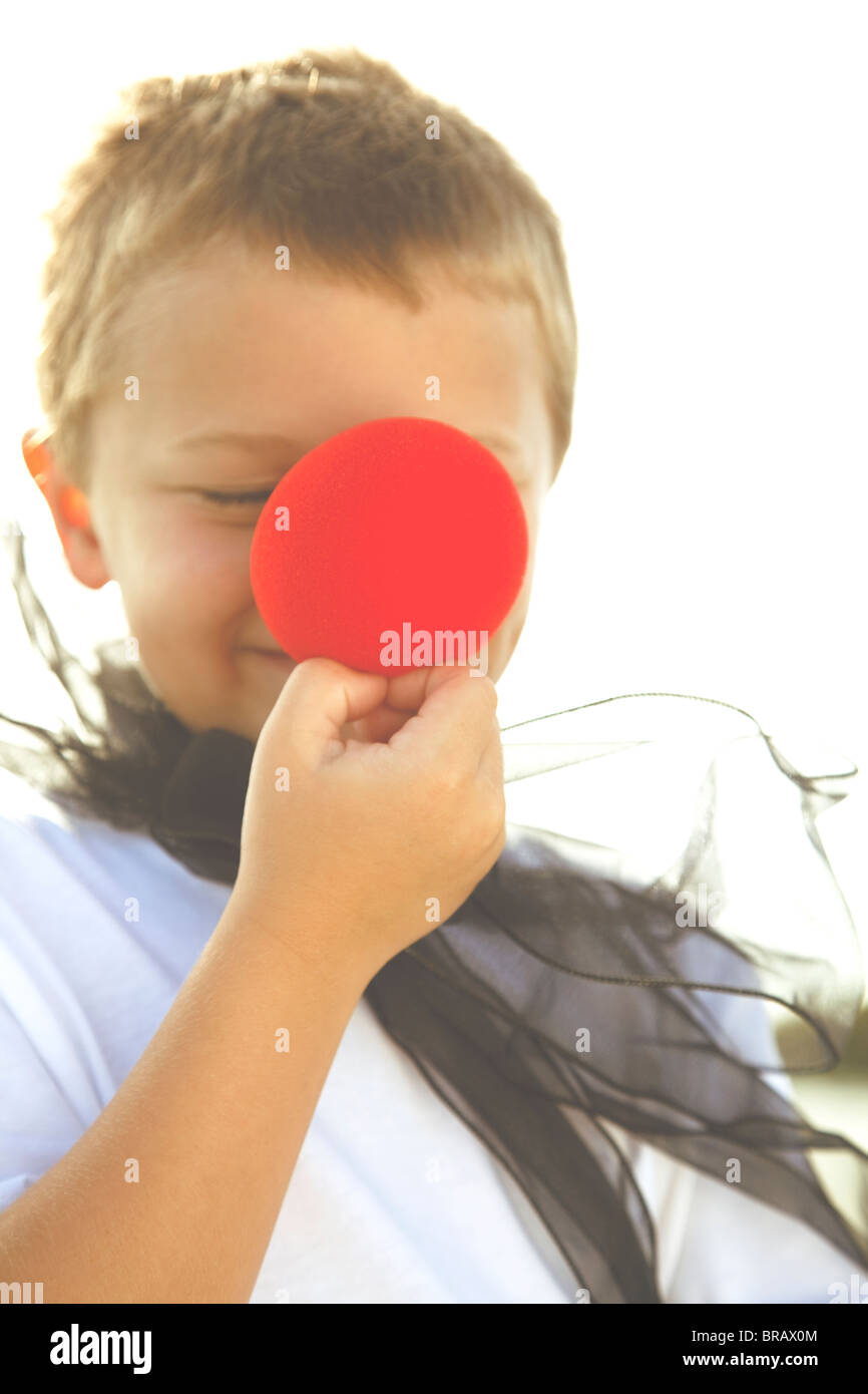 Boy with big red clown nose - Stock Image