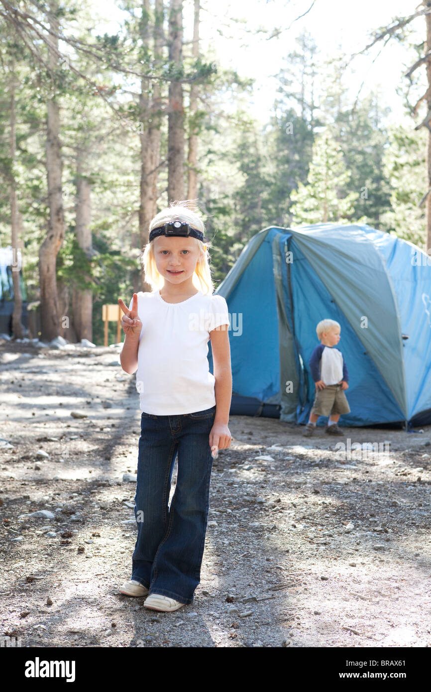 Small girl with headlamp at campsite - Stock Image