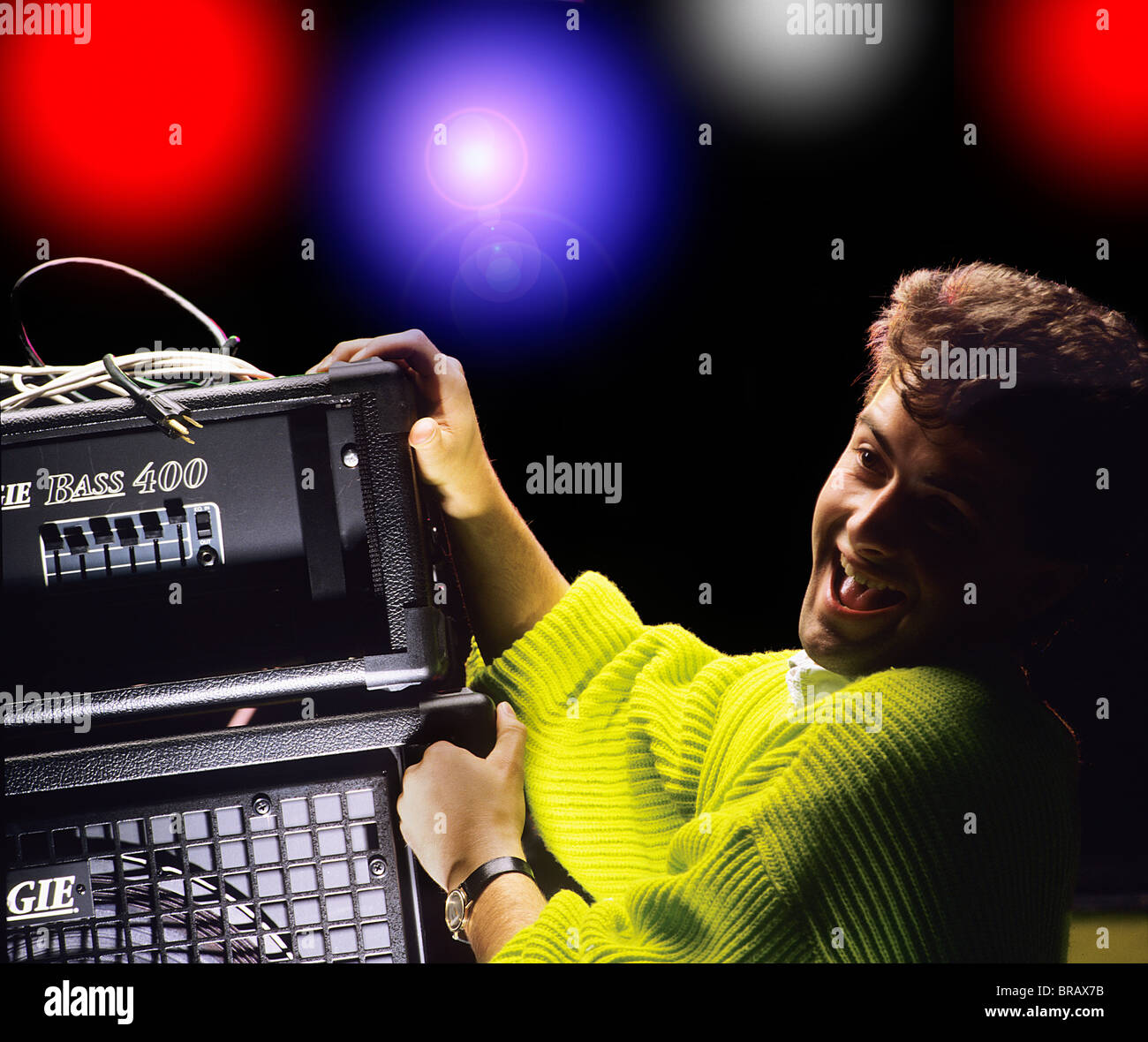 Roadie loading amplifier on stage, setting up for rock band or group - Stock Image