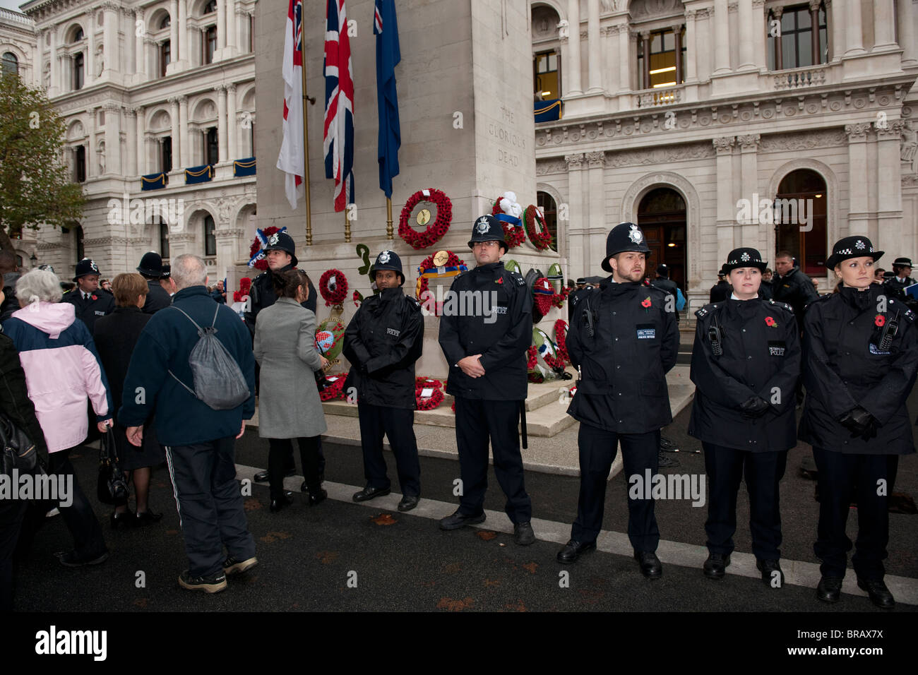A line of male and female Metropolitan Police officers guard The Cenotaph in Whitehall, London, after the remembrance - Stock Image
