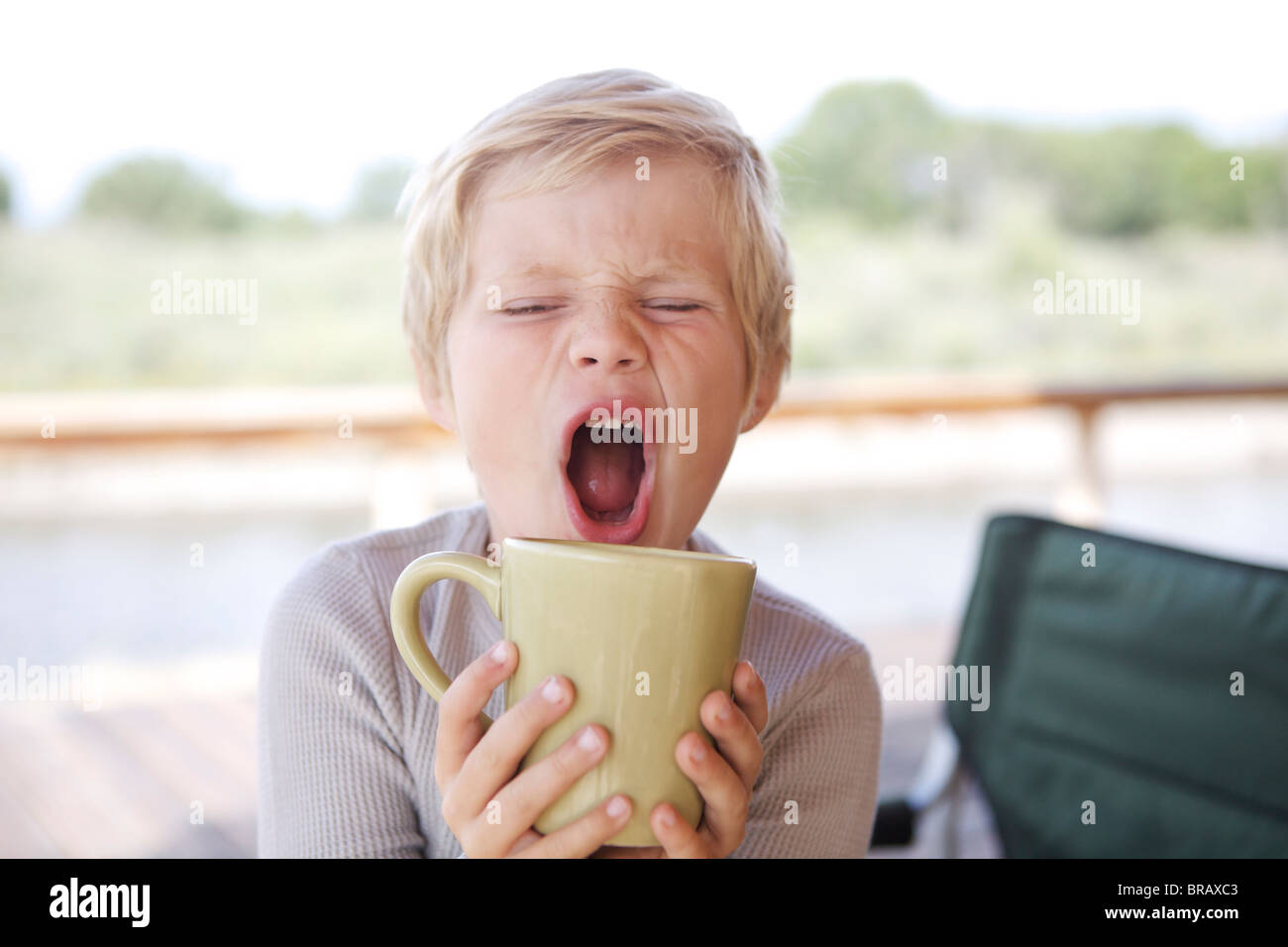 Young boy drinking from a coffee mug - Stock Image