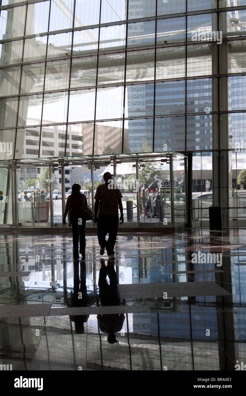 Silhouettes of a couple walking into the modern atrium lobby of the Aria Hotel in Las Vegas, Nevada, USA - Stock Image