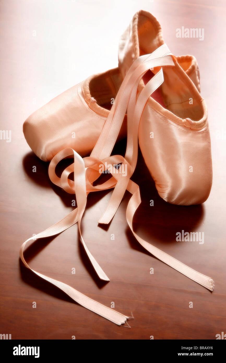 Pink satin ballet shoes on dark floor - Stock Image
