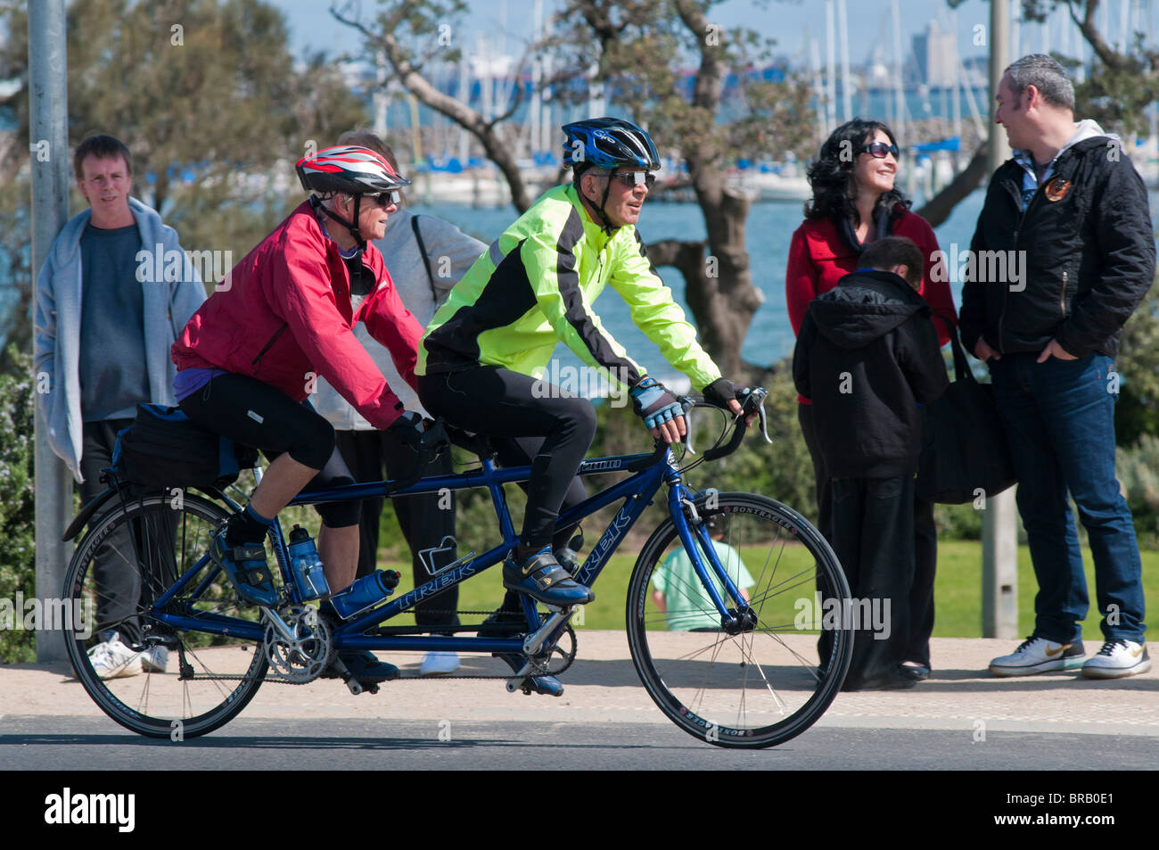 Couple riding a tandem bicycle along the Esplanade at St Kilda Beach in Melbourne Australia - Stock Image