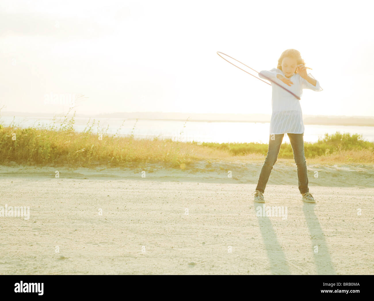 Girl playing with a hula hoop - Stock Image
