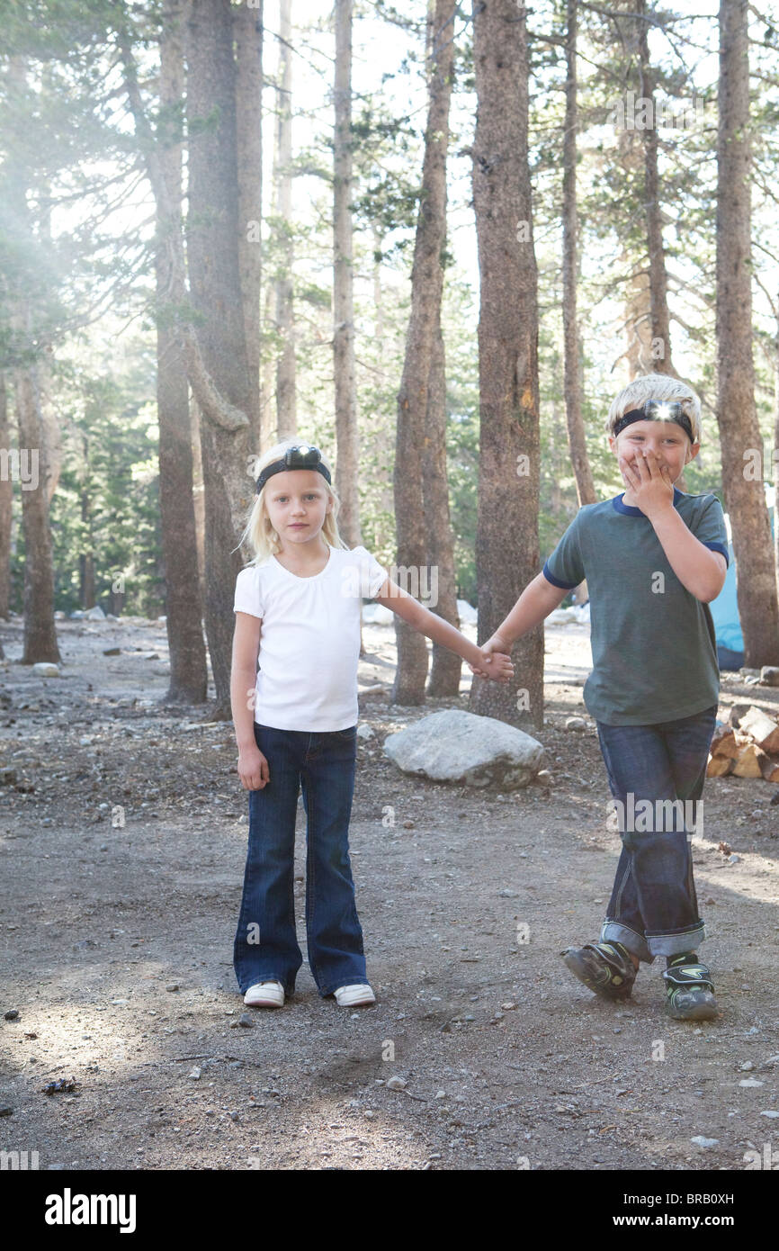 Boy and girl in woods with headlamps - Stock Image